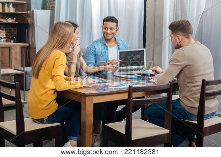 Friendly people. Clever enthusiastic emotional coworker feeling excited while sitting at the big table together and discussing their new interesting project