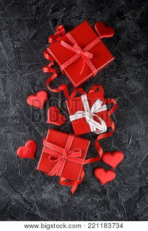 Red gift boxes tied with ribbons with bows and decorative silk hearts on a black background. Background for Valentine's Day. Flat lay. Top view.