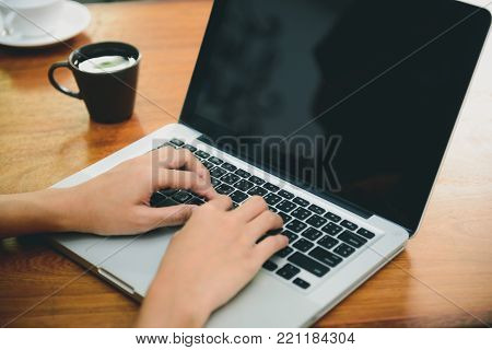 Business Technology Concepts - Digital lifestyle working outside office. Woman hands typing laptop computer with blank screen on table in coffee shop. Blank laptop screen mock up for display of design