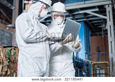 Portrait of two workers wearing biohazard suits using laptop  in industrial warehouse of modern waste processing plant