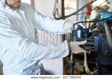 Portrait of unrecognizable factory worker wearing biohazard suits setting machine on modern processing plant