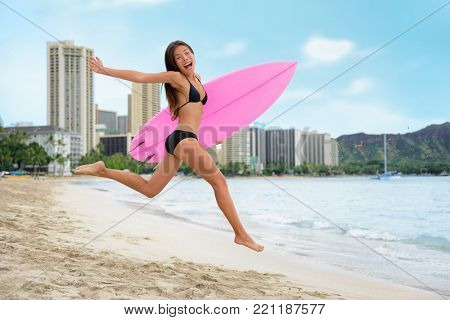 Surfing summer fun woman jumping of joy on beach with surfboard. Surf vacation lifestyle. Asian girl in bikini, sport and fitness active concept.