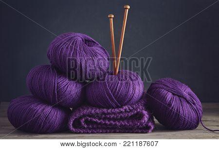Balls of purple merino wool, on table.