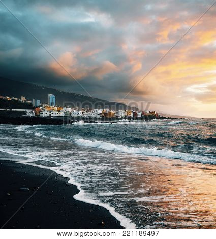 View of colorful houses of Puerto de la cruz, Jardin beach with black sand and Atlantic ocean at sunset, Tenerife, Canary islands, Spain