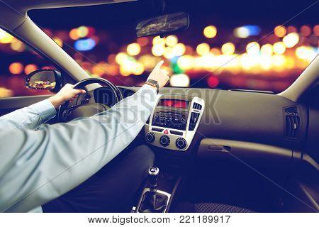 transport, business trip, direction and people concept - close up of young man driving car and pointing finger to something over city night lights background