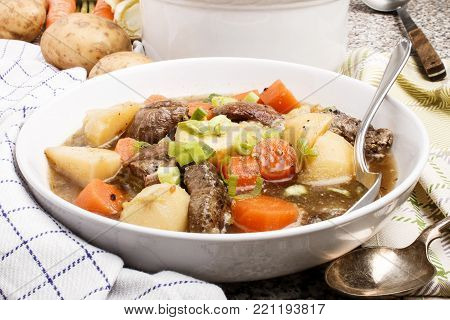 irish stew with beef, boiled potato and sliced carrot in a deep white plate