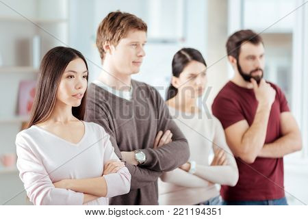 Good call. Focused earnest budding woman crossing arms while posing with three colleagues and looking straight