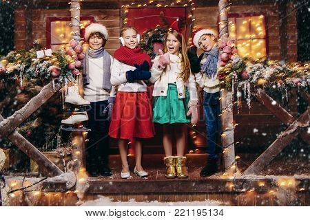 Four cheerful children in winter clothes and accessories stand near the house decorated for Christmas. Time for miracles. Merry Christmas and Happy New Year.