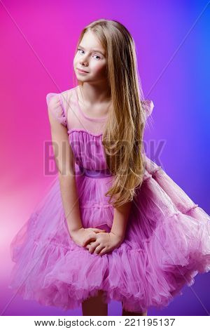 Portrait of a cute nine year old girl in an elegant dress over pink background. Children's beauty and health.