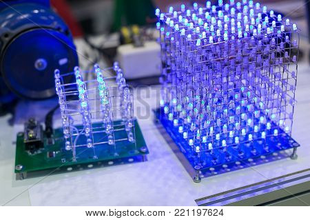 electricity, light, invention concept. on the work table there are amount of light emitting diodes that are connected with each other and composing geometrical figures