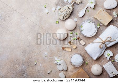 Spa setting from body care and beauty threatment products with flowers on stone background top view. Healthy and wellness concept. Flat lay.