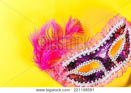 Mardi gras background with holiday mask, on bright yellow background copy space top view