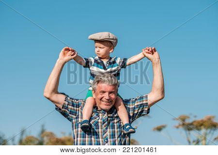 Grandfather carries grandson toddler boy on his shoulders. Child having piggyback ride on his grandfather's back outdoors.