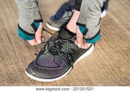 Close-up of the hands of a woman tying the shoelaces of her comfortable and flexible sport shoes before outdoor workout in a sunny day