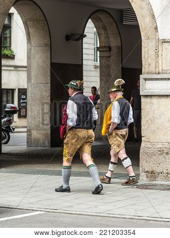 Munich, Germany - May 29, 2016: Men wearing the traditional Bavarian costume leather pants (lederhose) walk down the street in Munich, Bavaria, Germany.