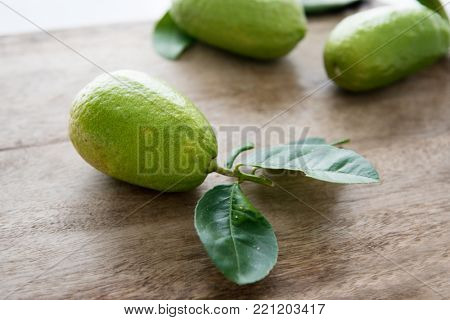 Fresh organic lemons with leaves on wood background, pesticide free, imperfect insect bites. poster