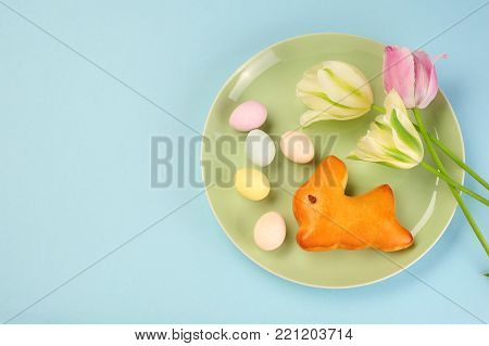 Easter bunny, Easter eggs and tulips ober blue background