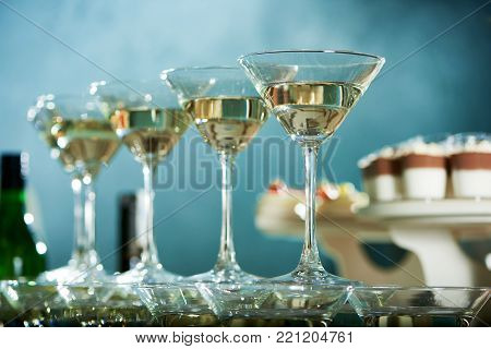 Perfectly polished martini glasses are standing on the blue background near candy-bar with different souffle and mousses.