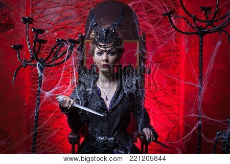 Woman in black dress holds a dagger. SHe sits on a throne.