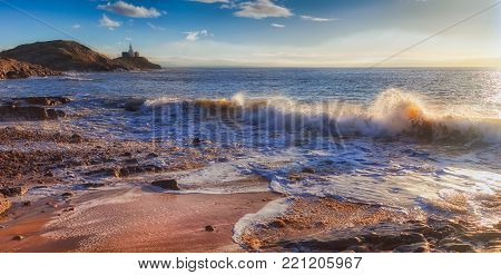 Back lit waves at Bracelet Bay, featuring the Mumbles Lighthouse on the Gower peninsula in Swansea, South Wales, UK