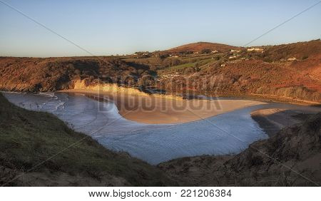 The beach at Three Cliffs Bay, a well known coastal beauty spot on the Gower peninsula in Swansea, South Wales, UK