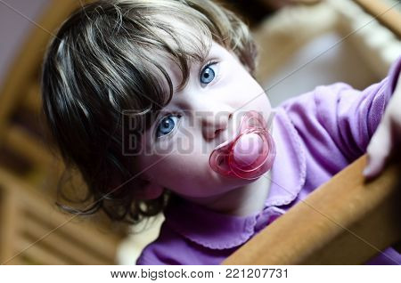 cute baby girl with blue eyes and a soother in her mouth