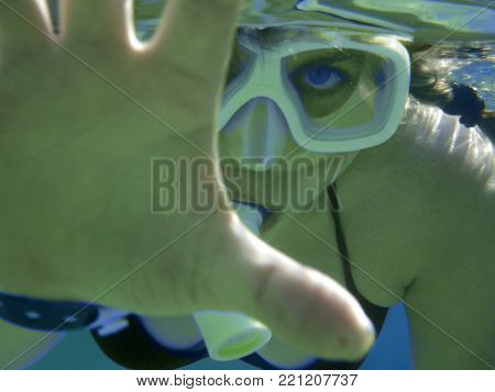 A woman swims under the water in a special mask does not allow herself to photograph herself.