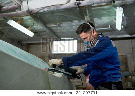 Side view portrait of mature modern man wearing respirator repairing boat in yacht workshop using electric polishing tool, copy space