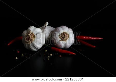 Kitchen still life with raw garlic bulbs, red chilli and colorful pepper spice on black background, Allium sativum vegetable.