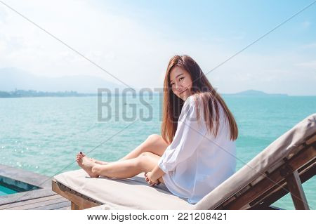 Portrait image of a happy beautiful asian woman on white dress sitting on sun bed by the sea with blue sky background
