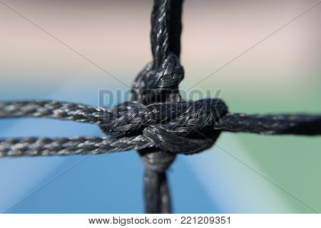 knot on a tennis net, close up black netting
