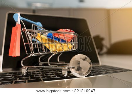 Shopsing online concept, Colorful paper shopping bag in trolley on laptop. Customer can buy everything from office or home and the messenger will deliver.
