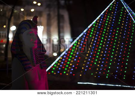 Belarus, Gomel, January 7, 2018. Miniature Egyptian statue of the pharaoh and pyramid of Cheops in New Year's lights
