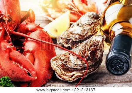 Fine selection of crustacean for dinner. Steamed lobster and oysters with bottle of white wine