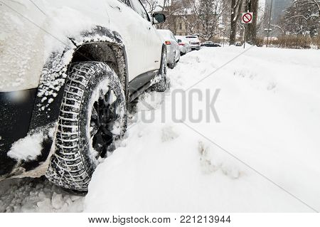 Winter driving and snow storm conceptual image with room for copy space closeup car in deep snow low angle view of tires on truck in deep snow conceptual insurance, winter driving safety and accident prevention background in bad weather