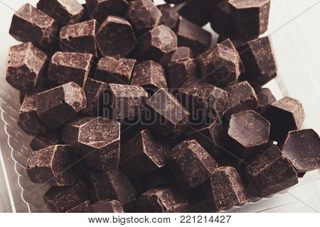 Closeup of chocolate morsels on white wood. Confectionery and dessert ingredients concept