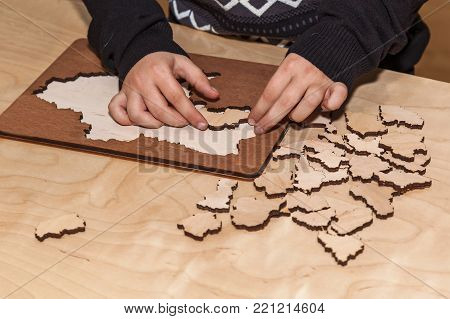 Man collects wooden puzzles on a wooden table