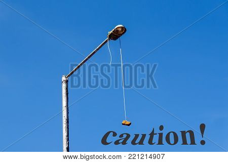 The brick hunging with the rope of the street lamp. A playful amusing signal, a appeal to watch carefully, with caution, forward and upwards while moving