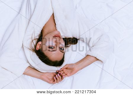 a young girl in a white terry robe lies on the bed early in the morning, under the eyes of patches