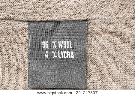 Fabric composition clothes label on knitted beige background closeup