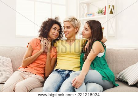 Happy female friendsin colourful clothes chatting at home. Three young women having friendly talk, gossiping and laughing, slumber party, copy space