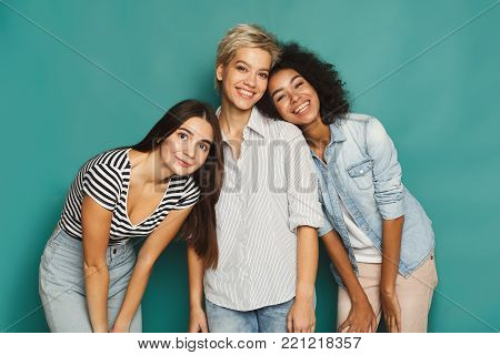 Happy female friends having fun at blue background. Three young women having friendly talk, gossiping and laughing, slumber party, copy space