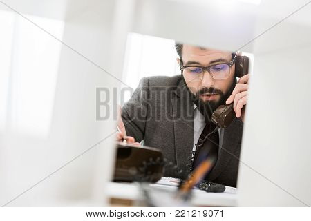 view through partition on businessman talking by stationary telephone in office