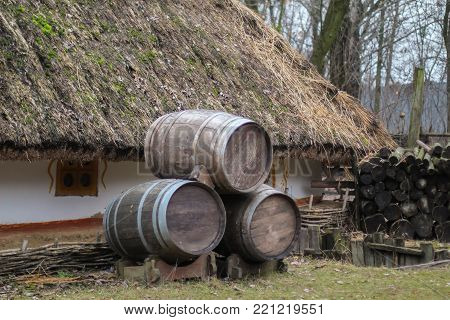 Three wooden barrels standing near the red wall of a house.beer barrels near Wattle and daub