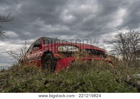 forgotten somewhere red car. neglected and broken car. a machine neglected on the background of a dramatic sky with beautiful gray clouds.