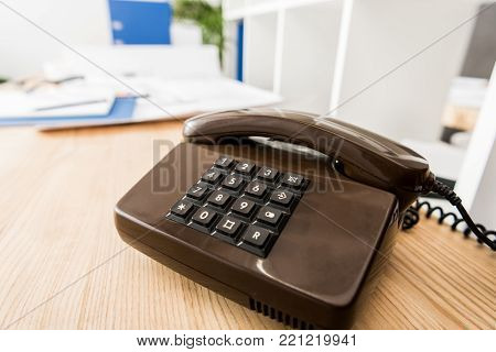 view of black stationary telephone on wooden table