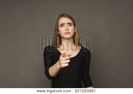 Sad girl pointing finger at camera. Young emotional woman gesturing right at you, brown studio background. Blaming, warning, accusing concept