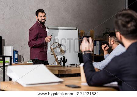 smiling businessman standing with pen near flipchart