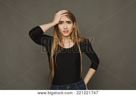 Regrets wrongdoing. Closeup portrait of confused young woman, slapping hand on head, having duh moment, brown studio background