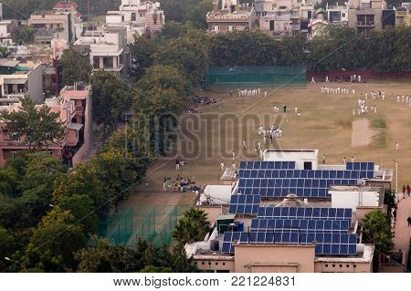 Children in white cricket uniforms playing on a field powered by solar panels. Perfect example of how alternate sources of energy are being adopted for public buildings in Noida Delhi